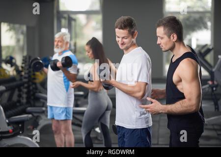 Entraîneur sportif musculaire, aidant l'homme à faire des exercices de levage avec dumbblells. Mettre en place des gens portant dans les vêtements de sport. Entraîneur féminin est concentré sur la clientèle personnes âgées l'élaboration. Banque D'Images