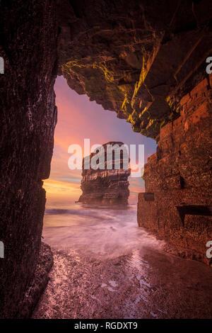 Coucher du soleil à Dun Briste pile la mer à partir d'une grotte sous Downpatrick Head. Le Comté de Mayo, Irlande. Banque D'Images