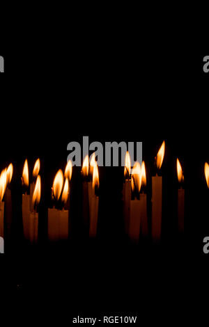 De nombreuses bougies de Noël dans la nuit sur le fond noir. Flamme de bougie set isolé en fond noir. Groupe de bougies allumées dans le noir avec Banque D'Images