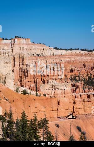 Bryce Canyon trail avec les randonneurs lointain en passant par rock arch sur ciel bleu ensoleillé jour au printemps Banque D'Images