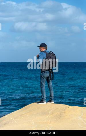 Un homme portant un sac à dos, debout sur le bord d'une roche calcaire surplombant la mer Banque D'Images