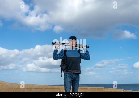 Un trépied photographe sur ses épaules Banque D'Images