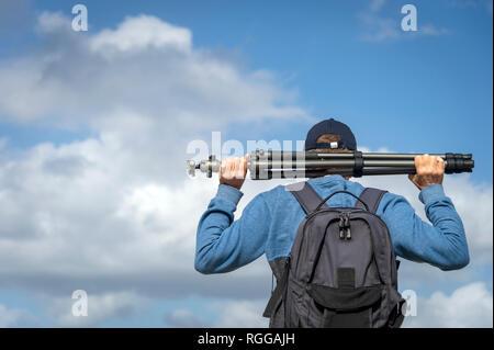 Vue arrière d'un homme portant un trépied photographique et portant un sac à dos Banque D'Images