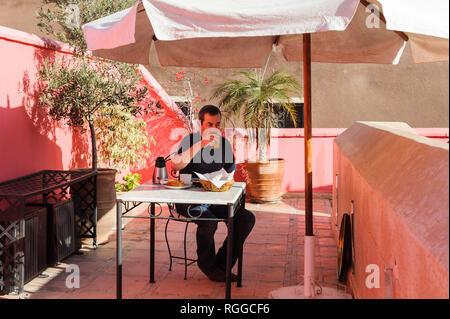 05-03-15, Marrakech, Maroc. Riad La Porte Royale. Un invité qui mange son petit-déjeuner sur la terrasse. Photo: © Simon Grosset Banque D'Images