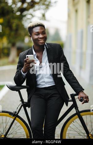 Jeune homme africain à l'extérieur, debout avec location, écouter de la musique avec des écouteurs