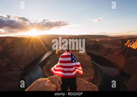 USA, Arizona, Colorado River, Horseshoe Bend, jeune homme sur viewpoint avec le drapeau américain
