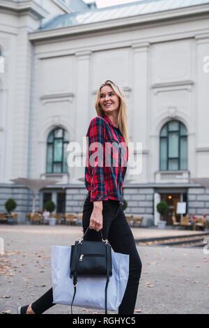 Portrait de jeune femme avec un sac à main et sac à marcher le long de Banque D'Images