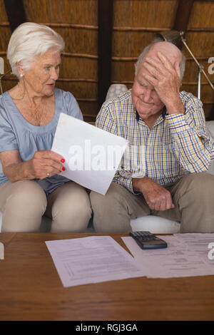 Vue avant du couple inquiet au cours de factures médicales dans la salle de séjour à la maison Banque D'Images