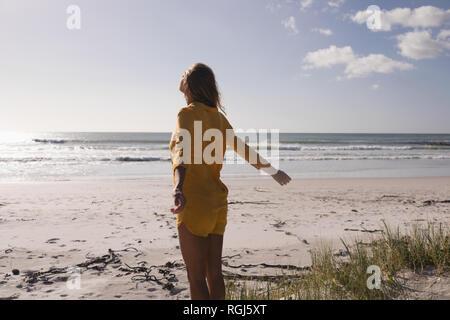 Jeune femme debout avec les bras tendus sur la plage