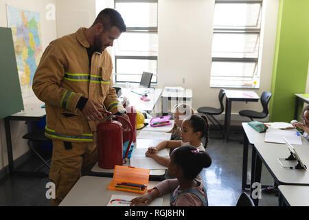 Vue latérale du Caucase mâle enseignement schoolkids pompier sur la sécurité incendie, l'extincteur de classe montrant dans l'école élémentaire Banque D'Images