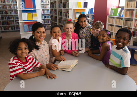 Vue avant du happy female teacher et schoolkids looking at camera while studying at table in school library Banque D'Images