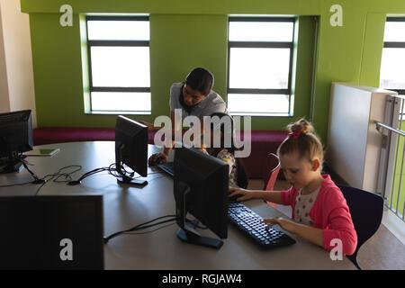 Professeur de droit à l'ordinateur d'enseignement à l'école bureau à schoolkid Banque D'Images