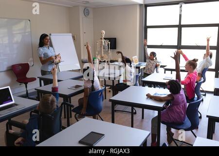 Vue latérale des mains tout en soulevant schoolkids sitting at desk in classroom of elementary school Banque D'Images
