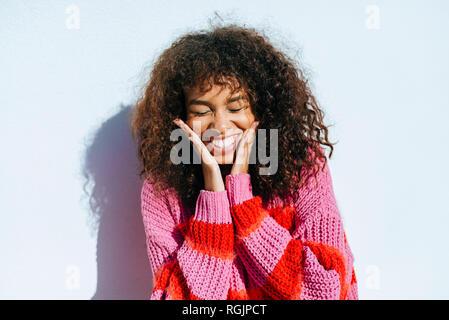 Portrait of laughing jeune femme avec des cheveux bouclés contre mur blanc Banque D'Images