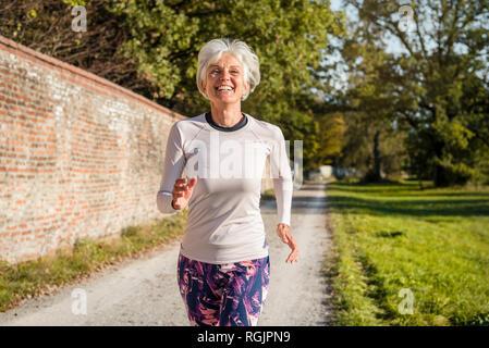 Happy senior woman running le long mur de briques dans un parc Banque D'Images