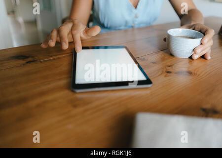 Close-up of woman sitting at table at home avec tasse de café et tablette