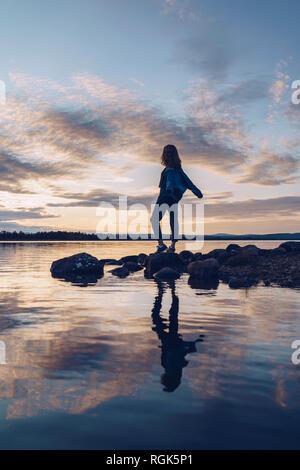 Jeune femme debout au bord du lac Inari, avec les bras tendus, Finlande