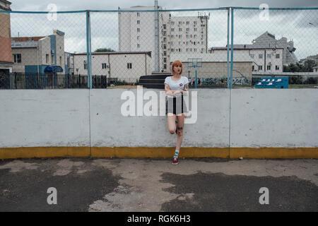 Jeune femme cool avec carver skateboard standing outdoors