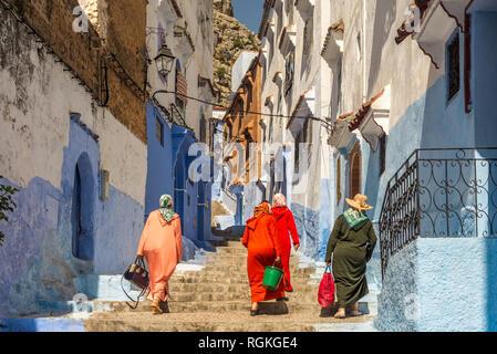 4 femmes en costume traditionnel en montant les escaliers dans la médina de Chefchaouen, la ville bleue au Maroc