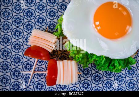 Bonjour. Délicieux petit déjeuner avec sandwich avec oeuf, jambon, fromage, pain grillé et salade se trouve sur une plaque avec de la tomate et de l'aneth Banque D'Images