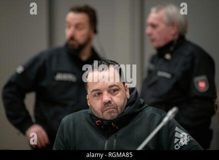 Oldenburg, Allemagne. 30Th Jan, 2019. Niels Högel, accusé du meurtre de 100 patients, est assis en face de deux fonctionnaires dans la salle d'audience le jour de l'essai. L'ex-infirmière, qui a déjà été condamné à la prison à vie pour deux meurtres en 2015, entre autres choses, a été le procès de nouveau depuis la fin du mois d'octobre 2018. Credit: Mohssen Assanimoghaddam/dpa/Alamy Live News Banque D'Images