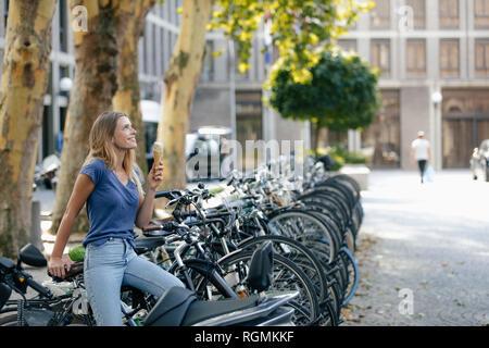 Pays-bas, Maastricht, smiling blonde young woman holding ice cream cone dans la ville au porte-vélo Banque D'Images
