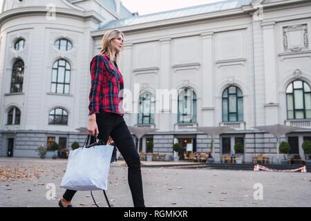 Jeune femme à la mode avec panier à marcher le long Banque D'Images