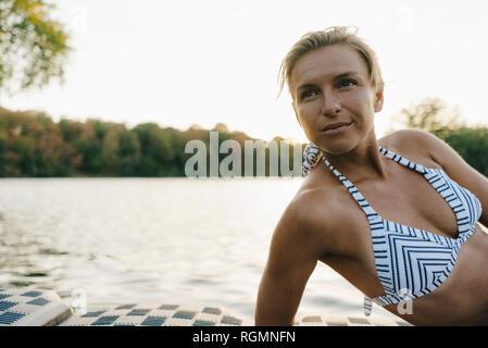 Portrait de femme portant un bikini au bord d'un lac