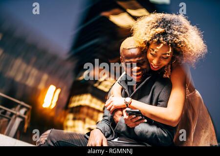 Jeune couple looking at smartphone par nuit
