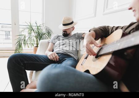Ambiance couple sitting on couch, femme jouant de la guitare à la maison