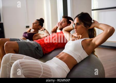 Les jeunes faisant des craquements sur un ballon de gymnastique Banque D'Images