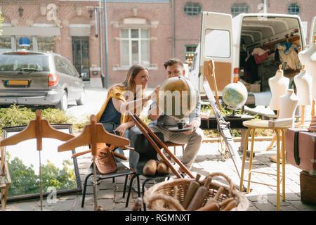 Belgique, Tongres, jeune couple sur un globe de l'examen du marché aux puces d'antiquités Banque D'Images
