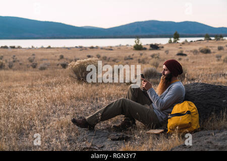 États-unis d'Amérique, Californie, jeune homme barbu à l'aide de téléphone cellulaire lors d'une pause en randonnée près de Lassen Volcanic National Park Banque D'Images