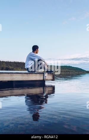 Jeune homme assis au bord du lac Inari, looking at view, Finlande Banque D'Images