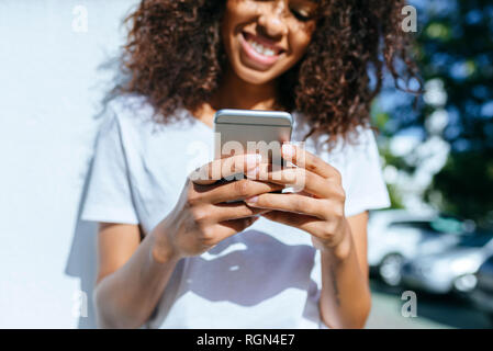 Mains de young woman holding smartphone, close-up Banque D'Images