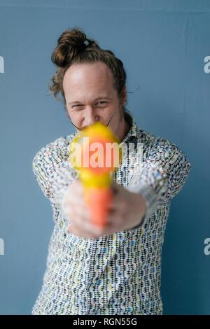 Portrait d'un homme avec moustache holding water gun au mur bleu Banque D'Images