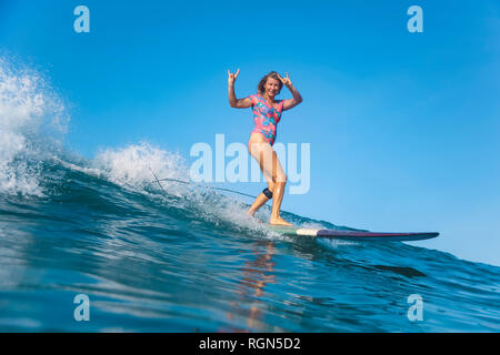 L'INDONÉSIE, Bali, Batubolong beach surf femme enceinte, faisant signe de les cornes Banque D'Images