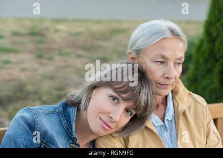 Portrait of young woman sitting on bench avec sa mère à l'extérieur