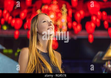 Femme célébrer le Nouvel An chinois regarder lanternes rouges chinois Banque D'Images