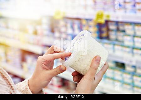 Les mains de l'acheteur avec récipient en plastique de fromage cottage à l'épicerie Banque D'Images