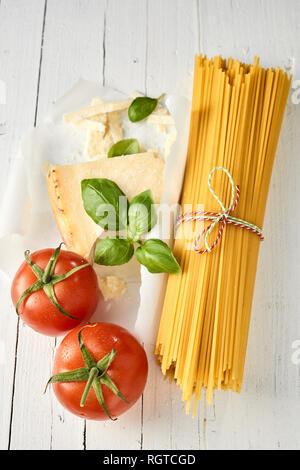 Spaghetti à l'Italienne au parmesan, tomates et basilic frais mûrs pour la préparation d'une cuisine méditerranéenne saine Banque D'Images