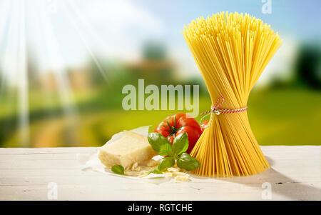 Paquet de spaghetti avec du parmesan, les feuilles de basilic vert frais et tomates sur une table d'extérieur dans le jardin avec des rayons de soleil de l'été Banque D'Images