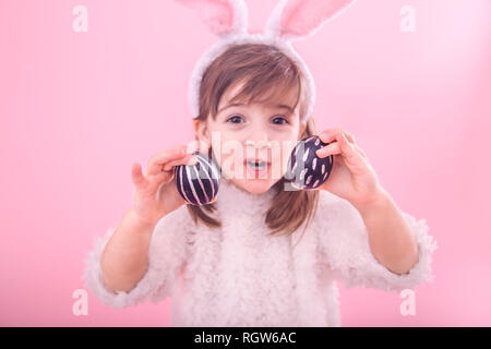 Portrait of a cute little girl avec oreilles de lapin et oeufs de Pâques, isolé sur fond rose Banque D'Images