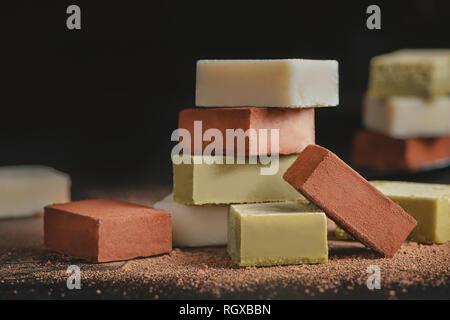 Assortiment de chocolats doux sur un fond noir avec copie espace. Lait et Chocolat gastronomique japonais Matcha close-up Banque D'Images
