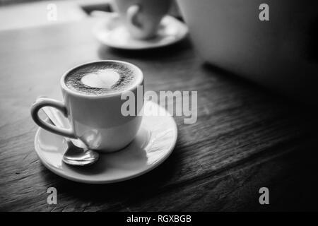 Un livre blanc tasse et soucoupe, cuillère en argent, remplie de café et une forme de coeur blanc latte art de mousse sur le dessus. Assis sur une table en bois, à côté d'un ordinateur portable. Banque D'Images