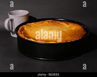 Gâteau au fromage frais cuit dans un ruisseau, forme, avec une tasse de café. Banque D'Images