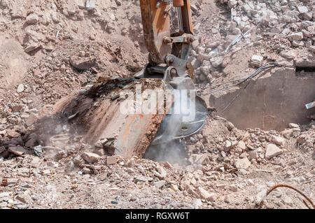 Sur un site de démolition le godet d'une pelleteuse tire sur une dalle en béton, vestiges de fondation d'un bâtiment.