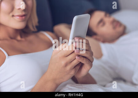 Cropped shot of young woman using smartphone pendant que mari sleeping in bed
