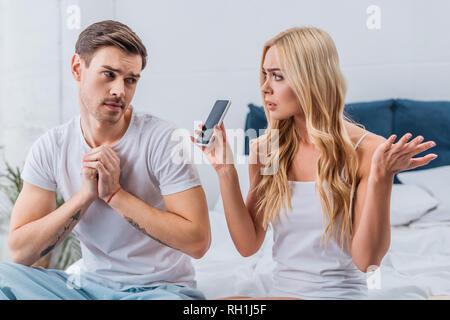 Femme confus montrant smartphone pour petit ami suspectes dans la chambre Banque D'Images