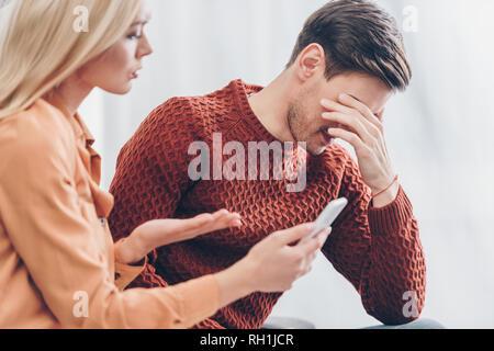 Jeune femme jalouse montrant smartphone pour perturber mari à la maison, concept méfiance Banque D'Images